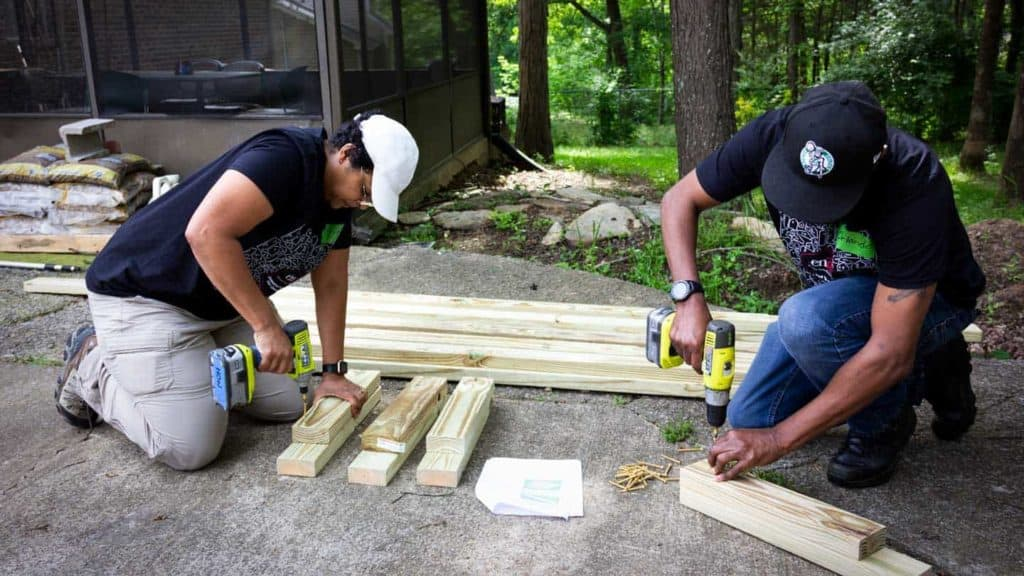 Two ENA team members drilling wood posts